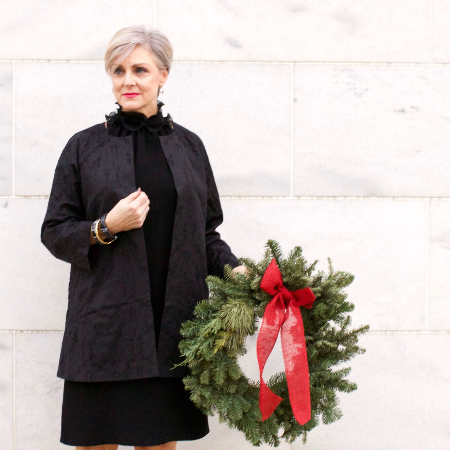 beth from Style at a Certain Age wears a Eileen Fisher shimmer jacquard 3/4 sleeve jacket and ruffled black dress