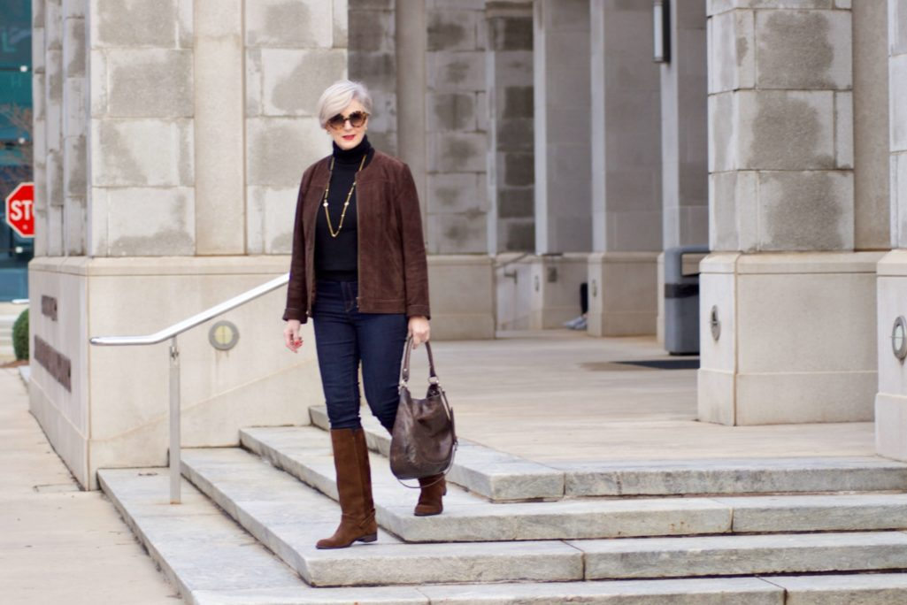 beth from Style at a Certain Age wears a black turtleneck, brown suede jacket, dark rinse denim and suede riding boots