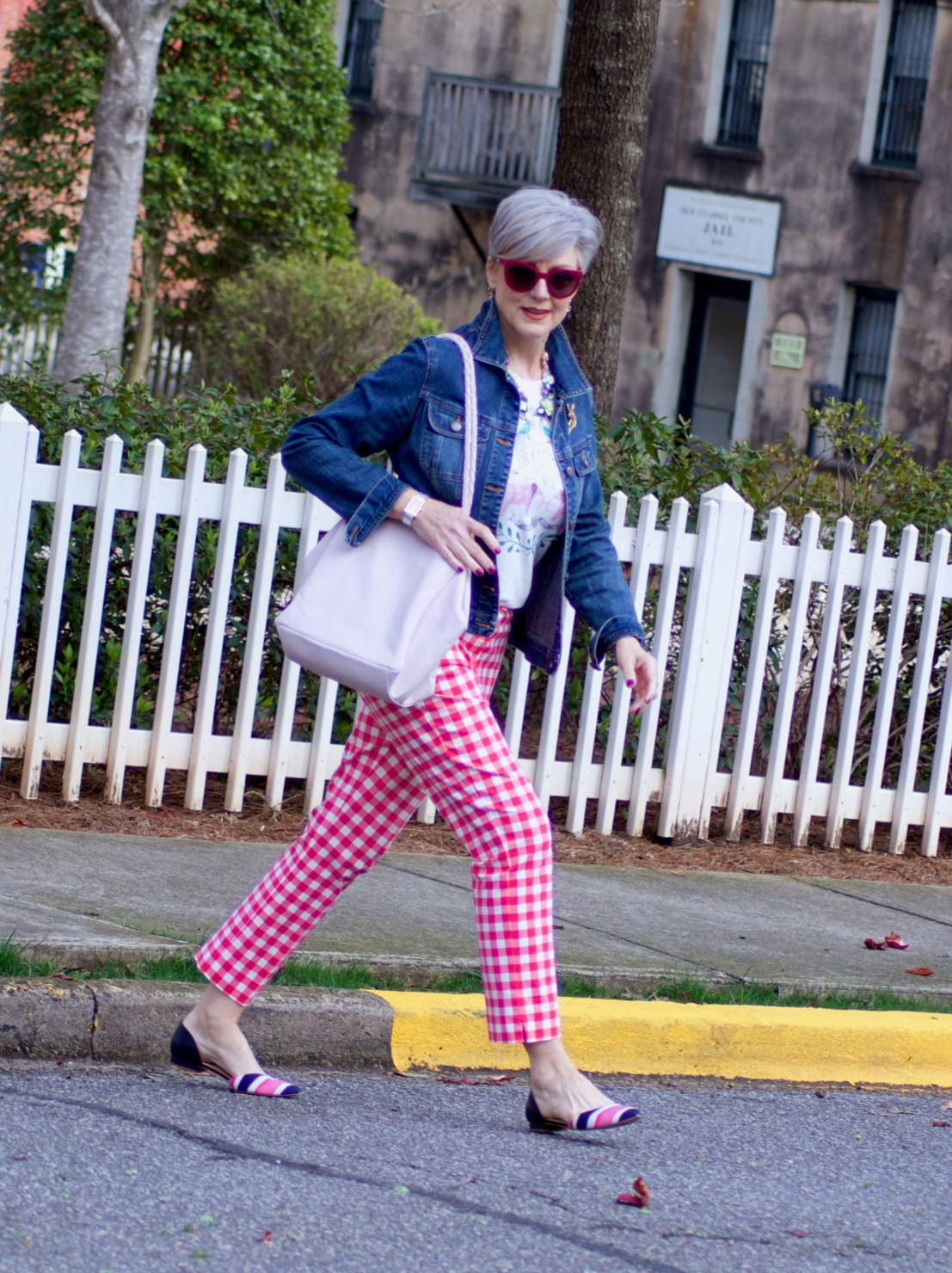 beth from Style at a Certain Age wears pink gingham pants, graphic tee, and denim jacket