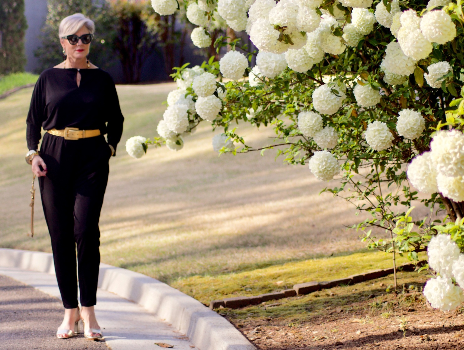beth from Style at a Certain Age wears a black jumpsuit, gold sandals, gold belt, and gold clutch handbag