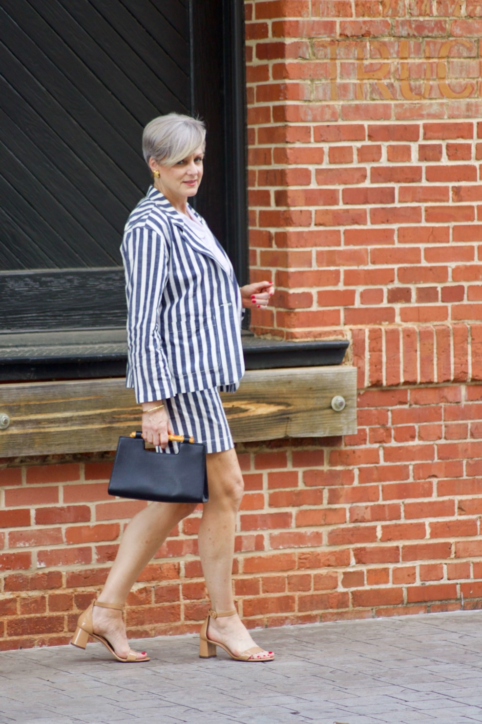 beth from Style at a Certain age wears stripe shorts, stripe blazer, white tee and nude sandals