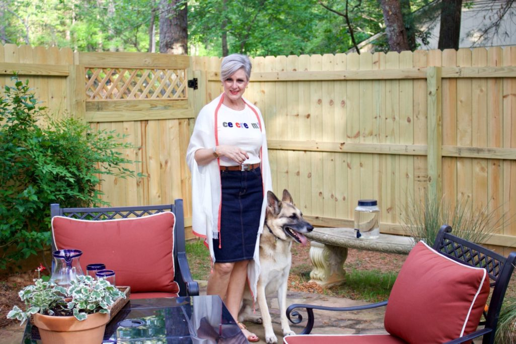 beth from Style at a Certain Age wears a J.Crew graphic tee, jean skirt, lightweight cape scarf, and Tory Burch sandals